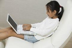 Ragazza in sedia facendo uso della vista laterale del computer portatile fotografia stock libera da diritti