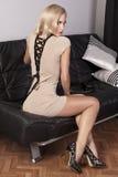 Ragazza sensuale che si siede su un sofà di cuoio nero fotografia stock