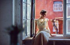 Ragazza sensuale molto bella in un vestito bianco che guarda dal Fotografia Stock Libera da Diritti