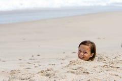 Ragazza sepolta in sabbia Fotografie Stock Libere da Diritti