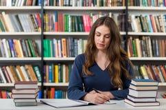 Ragazza seria che si siede ad uno scrittorio nella biblioteca con un aperto Immagine Stock