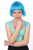 Ragazza seria con capelli blu che tengono il suo mento Fine in su Priorità bassa bianca Immagine Stock