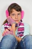 Ragazza seria con i manicotti dell'orecchio ed i guanti assettati Fotografia Stock Libera da Diritti