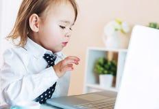 Ragazza seria del bambino che per mezzo di un computer portatile Fotografie Stock