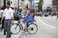 Ragazza seria in un vestito blu con i pois che attraversano la strada o Fotografia Stock