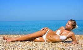 Ragazza sessuale che si distende su una spiaggia Fotografia Stock
