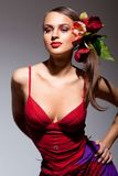 Ragazza sessuale in vestito rosso con i fiori in suoi capelli Fotografia Stock Libera da Diritti