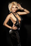 Ragazza sexy bionda sorridente che posa vestito nero d'uso Immagini Stock