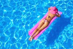 Ragazza sexy che galleggia su un materasso fotografie stock