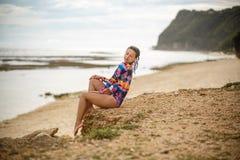 Ragazza sexy che posa seduta sulle rocce alla spiaggia immagine stock