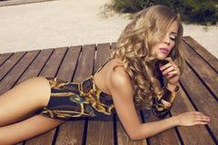 Ragazza sexy con capelli biondi lunghi nello swimsuite che posa sulla spiaggia Fotografia Stock