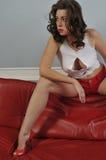 Ragazza sexy del brunette con i piedini lunghi che propongono al co rosso Fotografie Stock