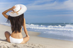Ragazza sexy della donna che si siede il cappello & il bikini di Sun sulla spiaggia Fotografia Stock Libera da Diritti