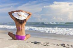 Ragazza sexy della donna che si siede il cappello & il bikini di Sun sulla spiaggia Fotografie Stock