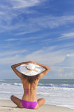 Ragazza sexy della donna che si siede il cappello & il bikini di Sun sulla spiaggia Immagini Stock