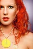 Ragazza sexy di redhead con un trucco insolito e un NEC Fotografie Stock