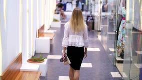 Ragazza sexy, donna bionda alta e bella che cammina giù il corridoio del centro commerciale, lungo le finestre dei negozi ed alla archivi video