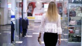 Ragazza sexy, donna bionda alta e bella che cammina giù il corridoio del centro commerciale, lungo le finestre dei negozi ed alla video d archivio
