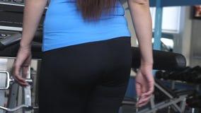 Ragazza sexy impegnata nella camminata sulla pedana mobile nel club di forma fisica Primo piano La ragazza sulla pedana mobile va archivi video