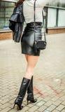 Ragazza sexy moderna alla moda in una gonna di cuoio nero su un'alta vita e di alti stivali su un tallone che posa sulla via Fotografia Stock