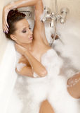 Ragazza sexy sensuale che si distende nella gomma piuma del bagno Immagini Stock
