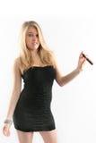 Ragazza sexy in un vestito nero, sigaro, fronte divertente. Fotografia Stock