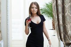 Ragazza sexy, vestito nero stretto, posante nel ristorante Immagine Stock