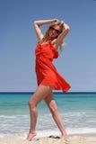 Ragazza sexy in vestito rosso ed occhiali da sole che stanno sulla spiaggia Fotografia Stock Libera da Diritti