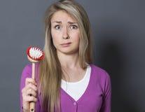 Ragazza sgomento 20s con la spazzola del piatto a disposizione infelice al lavaggio ed alla pulizia immagini stock