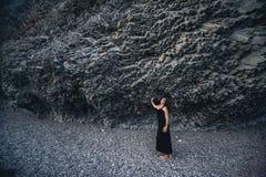 Ragazza snella nel vestito nero lungo che sta vicino alla roccia Immagini Stock Libere da Diritti