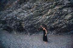Ragazza snella nel vestito nero lungo che sta vicino alla roccia Fotografie Stock Libere da Diritti