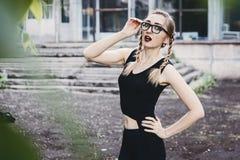 Ragazza snella in vestito nero con le trecce ed i vetri fotografia stock