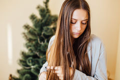 Ragazza sola che si siede dietro l'albero di Natale con i presente Fotografia Stock