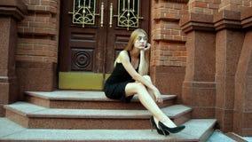 Ragazza sola che si siede sulle scale in vestito nero video d archivio