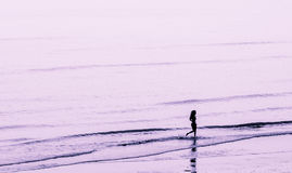 Ragazza sola su una spiaggia Fotografia Stock