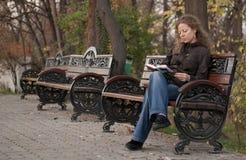 Ragazza sola in una lettura della sosta Fotografie Stock