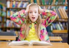 Ragazza sorpresa che legge un libro nella biblioteca Fotografia Stock Libera da Diritti