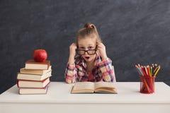 Ragazza sorpresa che si siede con i libri alla tavola Immagini Stock