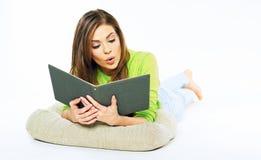 Ragazza sorpresa che si trova sul pavimento che tiene un libro Giovane donna p Fotografia Stock
