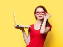 Ragazza sorpresa della testarossa con il computer portatile fotografia stock libera da diritti