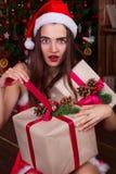 Ragazza sorpresa di Santa in cappelli di Santa che aprono il contenitore di regalo vicino al christm Fotografia Stock