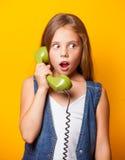 Ragazza sorpresa giovani con il microtelefono verde fotografia stock libera da diritti