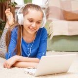 Ragazza sorridente adolescente che per mezzo del computer portatile sul pavimento Immagine Stock Libera da Diritti