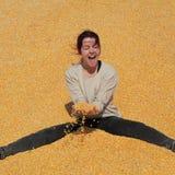 Ragazza sorridente al mucchio di cereale dopo il raccolto fotografie stock