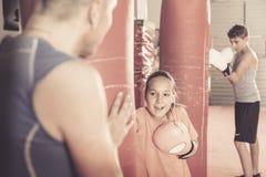 Ragazza sorridente all'allenamento di pugilato alla palestra sul punching ball Immagine Stock