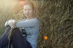 Ragazza sorridente all'aperto con i chiarori del sole e del fieno Fotografia Stock