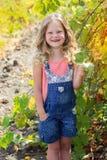 Ragazza sorridente bionda del bambino nella vigna dell'uva Fotografia Stock