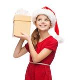 Ragazza sorridente in cappello dell'assistente di Santa con il contenitore di regalo Immagini Stock