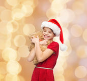 Ragazza sorridente in cappello dell'assistente di Santa con l'orsacchiotto Fotografia Stock Libera da Diritti