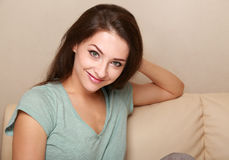 Ragazza sorridente casuale che si siede sul sofà Fotografia Stock Libera da Diritti
